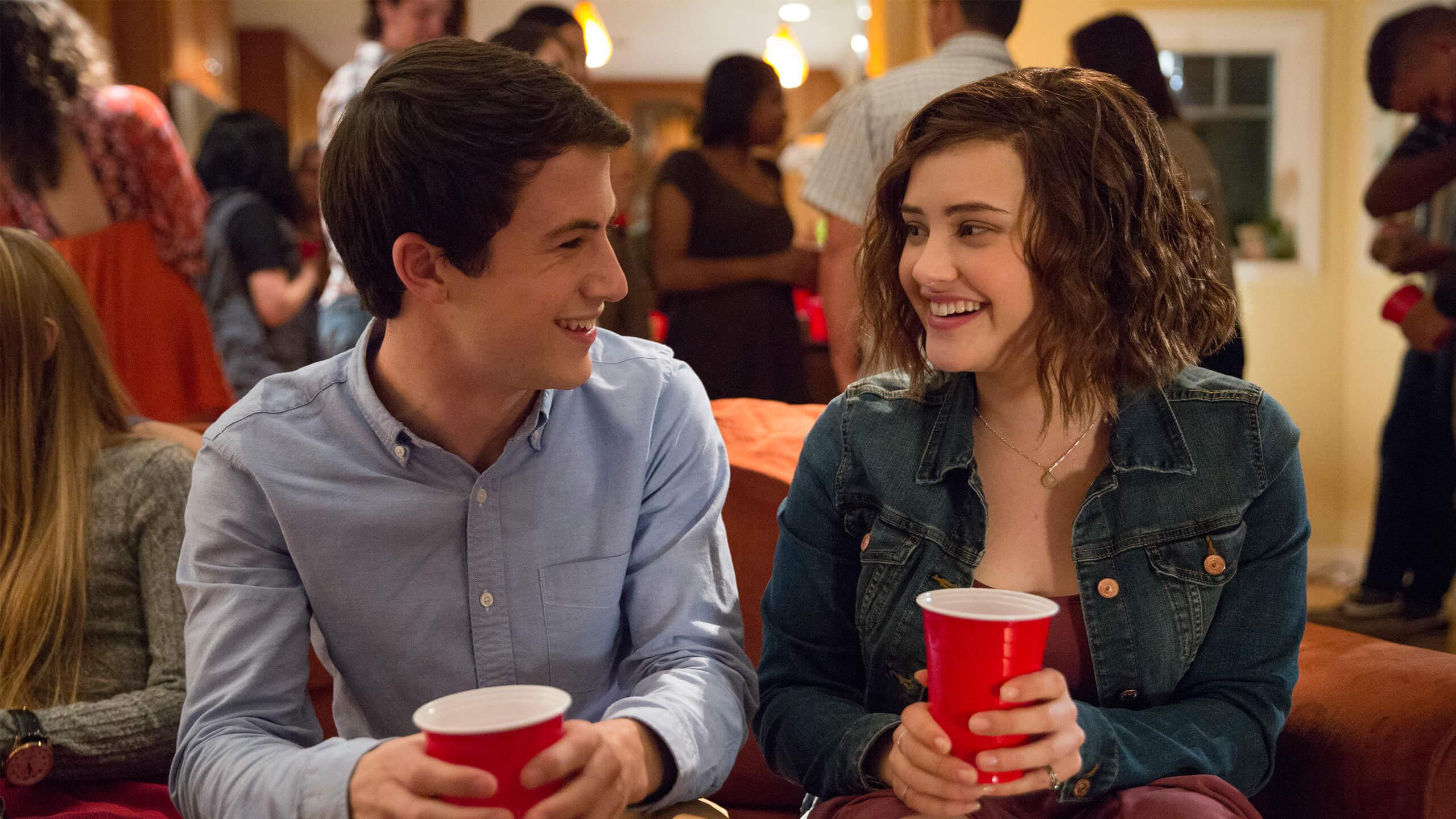 Clay und Hannah sitzen auf einer Couch.