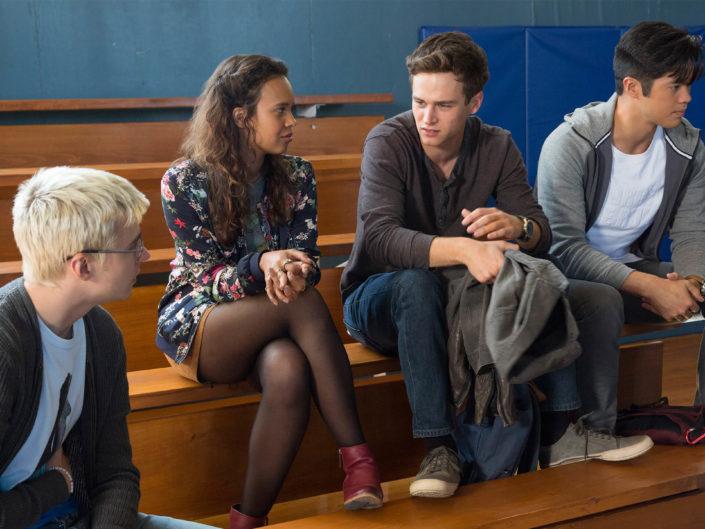 Alex, Jess, Justin und ach sitzen auf Bänken und unterhalten sich.