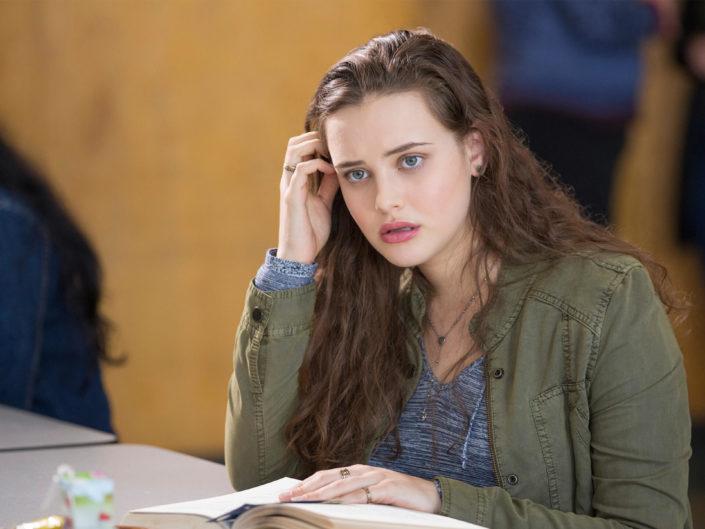 Hannah sitzt an einem Tisch und schaut nachdenklich.