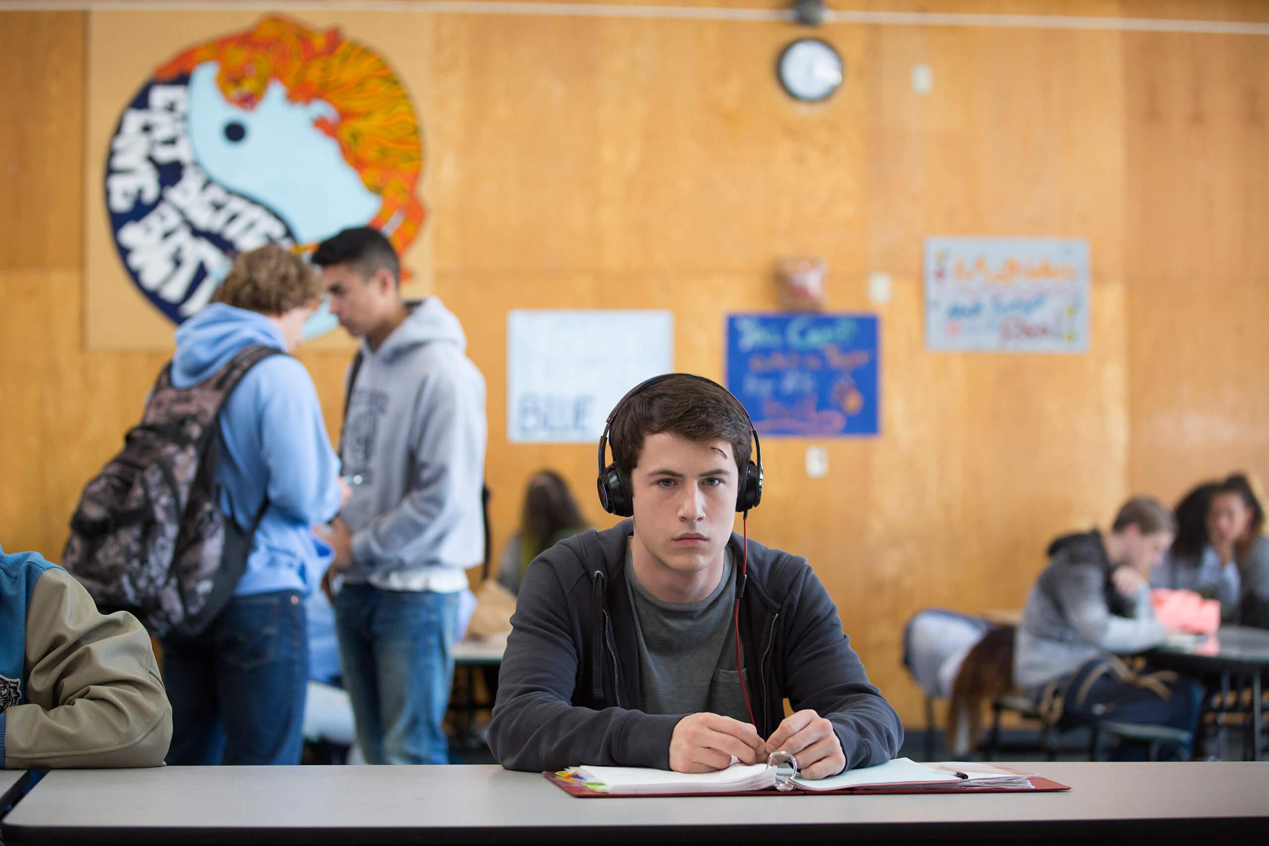 Clay sitzt mit Kopfhörern an einem Tisch in der Mensa.