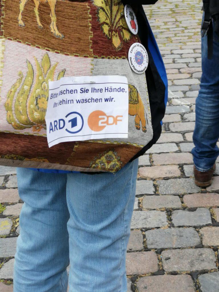 """Ein Zettel an der Tasche einer Demonstrantin, auf dem steht: """"Bitte waschen Sie Ihre Hände. Ihr Gehirn waschen wir."""", gefolgt von den Logos von ARD und ZDF."""