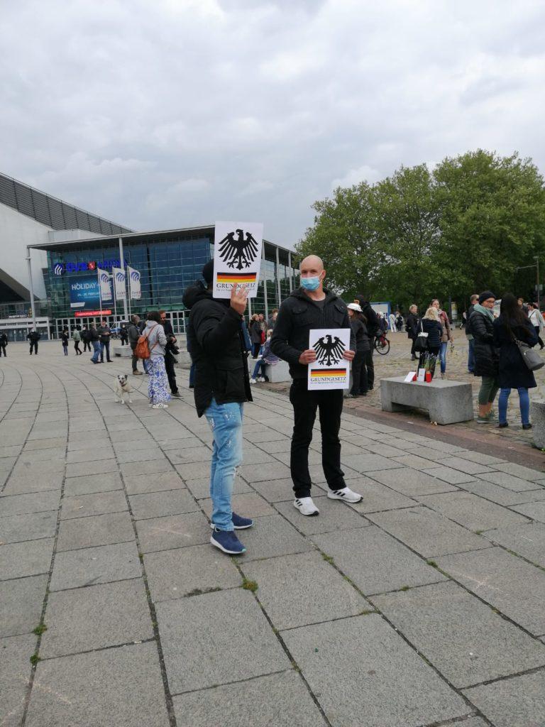 Zwei Männer auf der Demonstration, sie halten je ein Blatt mit dem Bundesadler, der deutschen Fahne und dem Schriftzug Grundgesetz der Bundesrepublik Deutschland.