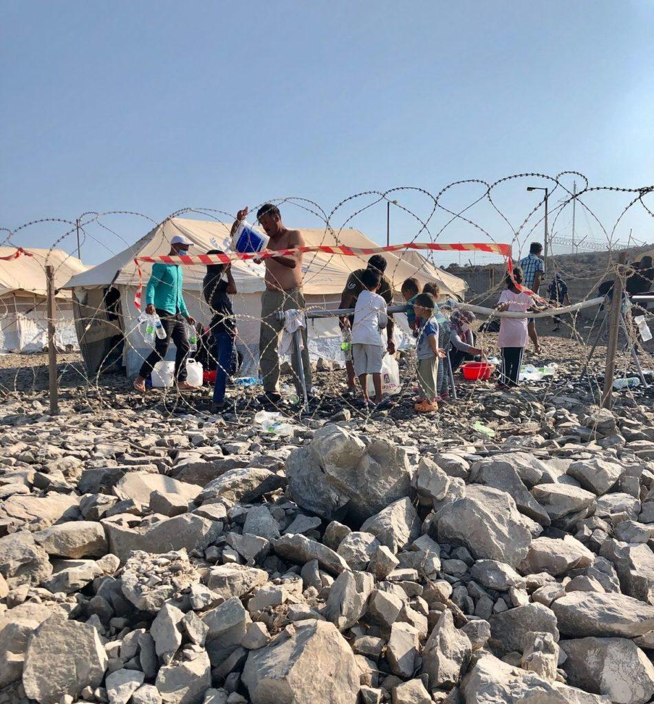 Katastrophale hygienische Bedingungen. Erwachsene und Kinder waschen sich unter freiem Himmel mit Wasser aus Eimern.